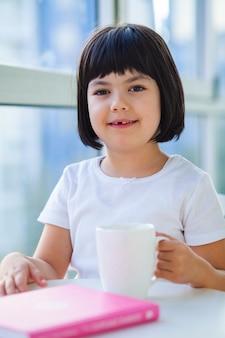 Niña bebiendo té de leche en casa
