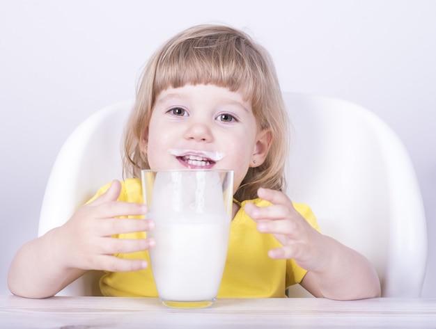 Niña bebiendo un vaso de leche en casa con bigote de leche