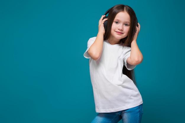 Niña de belleza en camiseta y auriculares con cabello largo