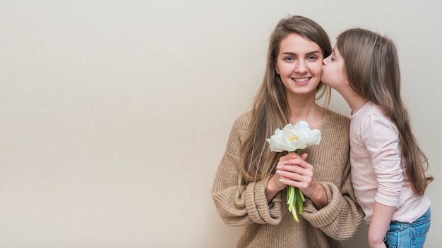 Niña besando a la madre con tulipanes en la mejilla