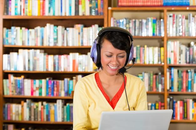Niña en biblioteca con laptop y auriculares