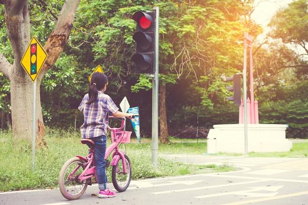 La niña va en bicicleta por el parque, se detiene en el semáforo.