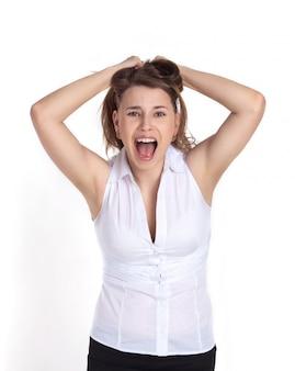 Una niña en un blanco aislado gritando de frustración, tirando de su cabello en su cabeza.