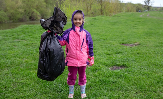 Una niña con una bolsa de basura en un viaje a la naturaleza para limpiar el medio ambiente.