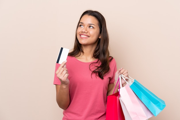 Niña con bolsa de compras con bolsas de compra y una tarjeta de crédito