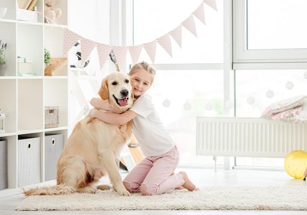 Niña bonita abrazando lindo perro