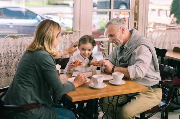Niña bonita. abuela de pelo rubio cuidando a su hermosa linda niña pasando la mañana en la cafetería