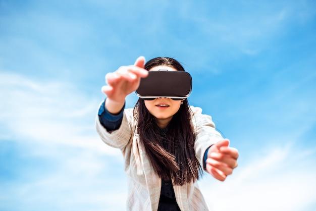 Niña bonita al aire libre disfrutando de gafas de realidad virtual