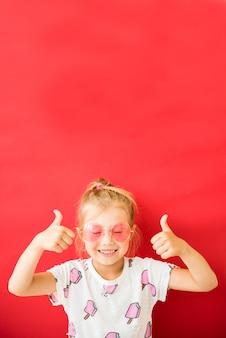 Niña bonita alegre en gafas de color rosa que muestran los pulgares para arriba en rojo