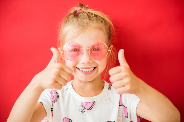 Niña bonita alegre en gafas rosas mostrando los pulgares hacia arriba sobre rojo
