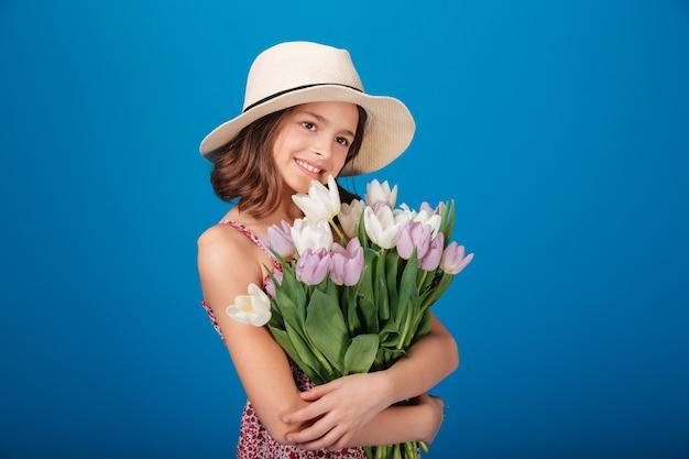 Niña bonita alegre con sombrero sosteniendo ramo de flores sobre fondo azul.