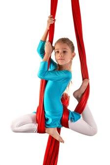 Niña bonita alegre en un traje de gimnasia azul hace trucos en una cinta de aire roja sobre un blanco