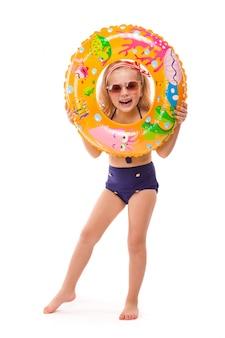 Niña bonita en bikini rojo a rayas, pantalones azules, gafas de sol y soporte de corona rosa con anillo de goma en la mano