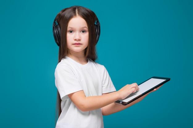 Niña bonita en camiseta y auriculares con cabello largo, con tableta en las manos