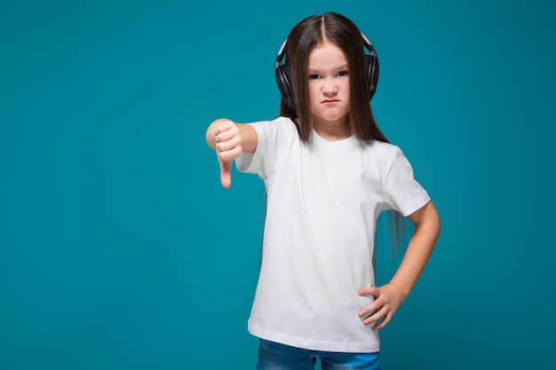 Niña bonita en camiseta y auriculares con pelo largo