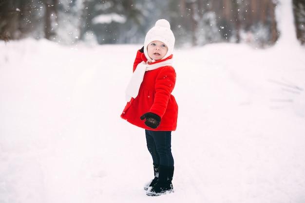 Niña bonita en capa roja en bosque de invierno. niña divirtiéndose en día de invierno. niña alegre en guantes y sombrero blanco corre sobre blanco como la nieve