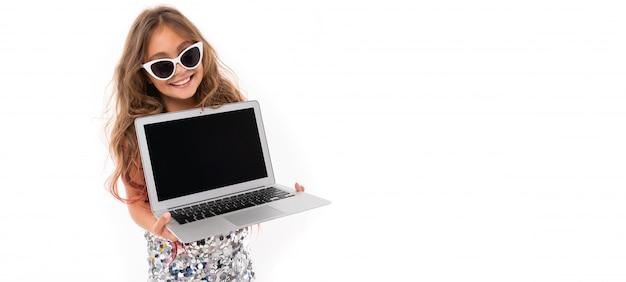 Niña bonita caucásica con gafas de sol y portátil, pianorama aislado sobre fondo blanco.