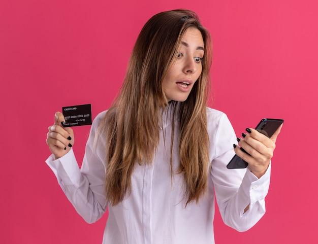 Niña bonita caucásica joven sorprendida tiene tarjeta de crédito y mira el teléfono aislado en la pared rosa con espacio de copia