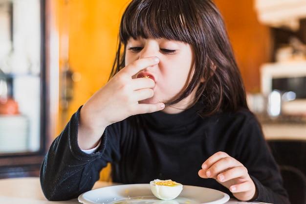 Niña bonita comiendo la mitad de huevo en la cocina