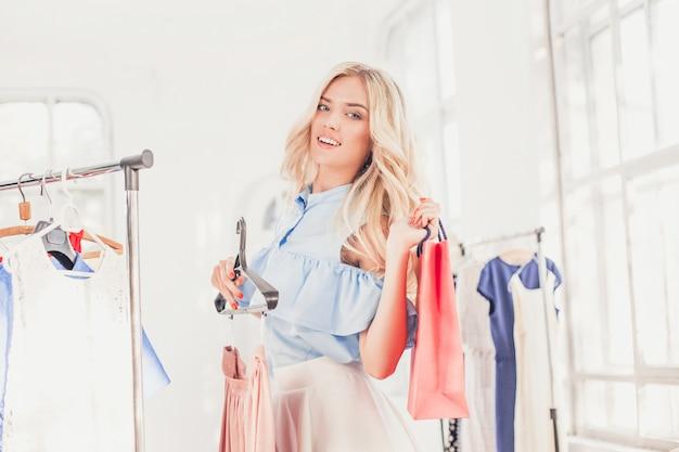 La niña bonita eligiendo y probándose vestidos en la tienda