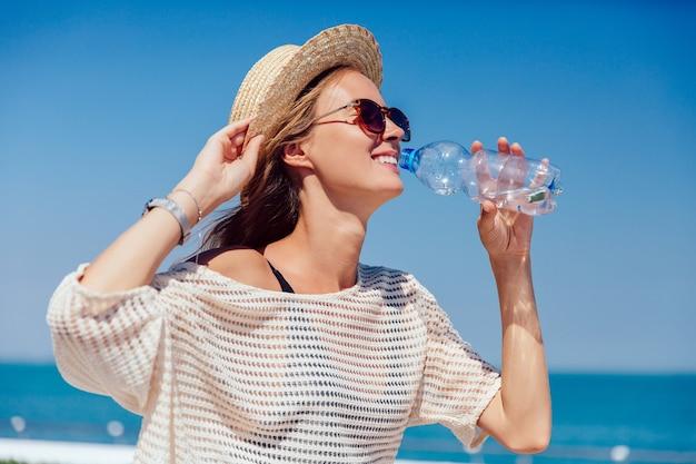 Niña bonita feliz en gafas de sol bebiendo agua clara, durante la caminata en el muelle