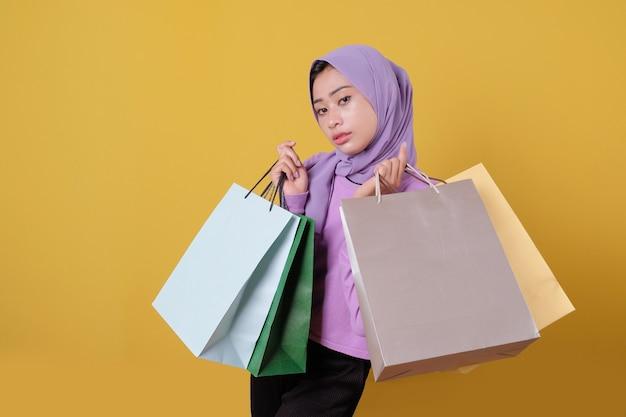 Niña bonita feliz sonriente con tarjeta de crédito para gastar algo de dinero en el centro comercial, sosteniendo bolsas de compras, comprar regalos o regalos, darse un capricho día