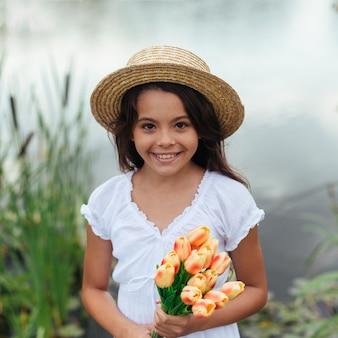 Niña bonita con flores junto al lago