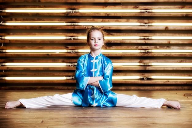 Niña bonita en la habitación en ropa deportiva para artes marciales es wushu o kung fu