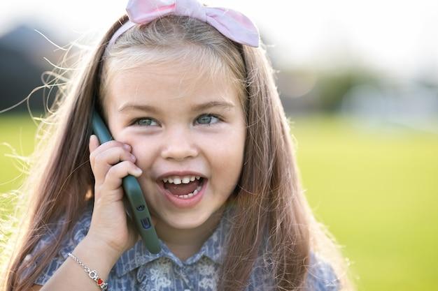 Niña bonita hablando por teléfono móvil sonriendo felizmente al aire libre en verano.