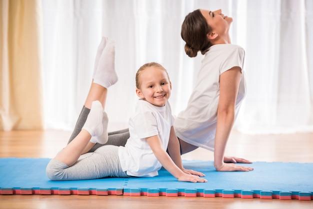 Niña bonita haciendo ejercicios de yoga en la alfombra en casa.