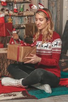 Niña bonita en una imagen de año nuevo entre los regalos y decoraciones navideñas