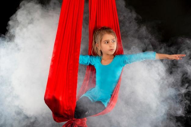 Niña bonita intrépida en un traje de gimnasia azul en una cinta roja aérea con humo alrededor