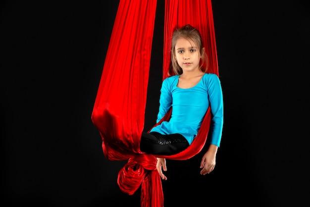 La niña bonita intrépida en un traje de gimnasia azul muestra una cinta roja aérea de acrobacias en negro