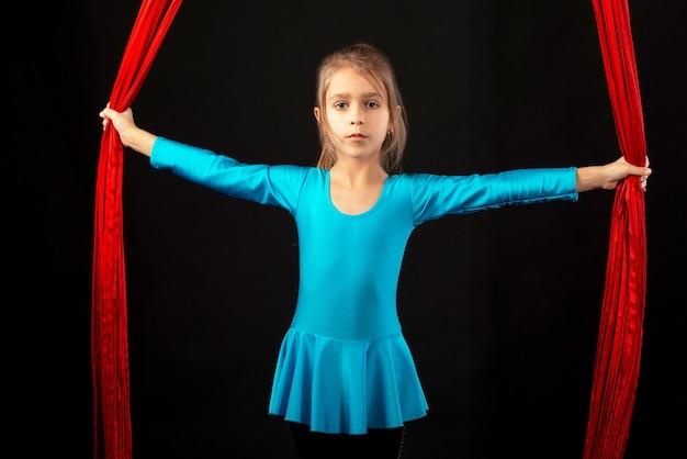 Niña bonita intrépida en un traje de gimnasia azul muestra una cinta roja aérea de acrobacias en un negro