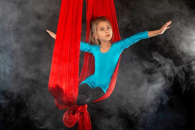 La niña bonita intrépida en un traje de gimnasia azul muestra una cinta roja aérea de acrobacias rodeada de humo