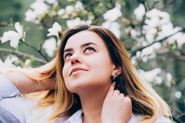 Una niña bonita en un jardín disfruta de florecientes árboles de magnolia