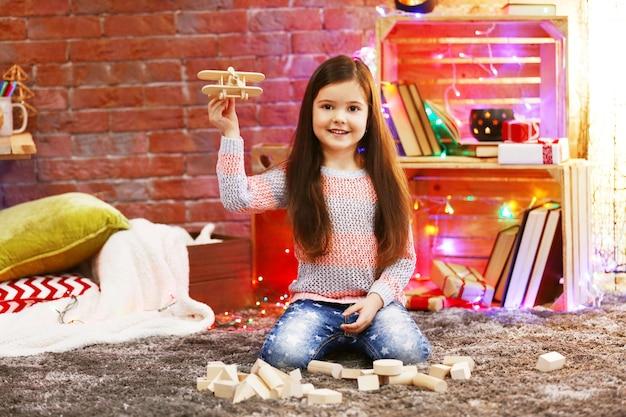Niña bonita jugando con avión de madera en la habitación decorada de navidad