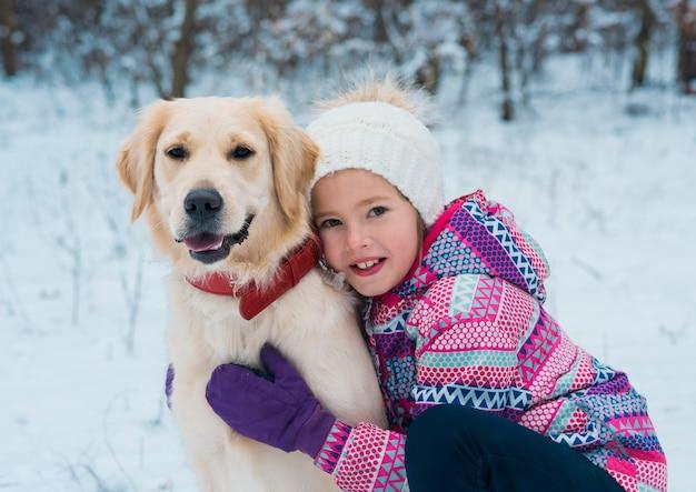Niña bonita jugando con su perro en un día de invierno