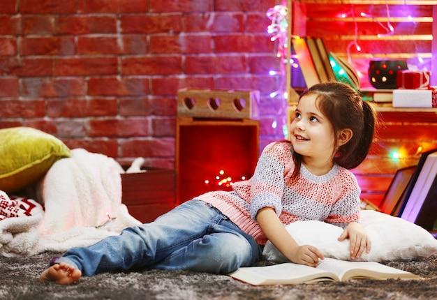 Niña bonita con libro en habitación decorada de navidad