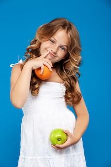 Niña bonita con manzana y naranja sobre pared azul