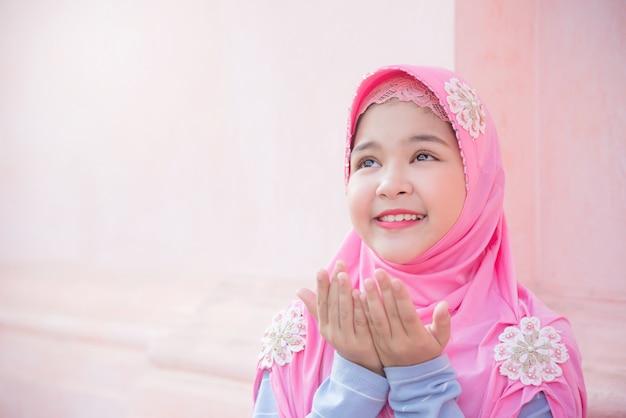 La niña bonita musulmana está levantando las manos, pide la bendición de dios.