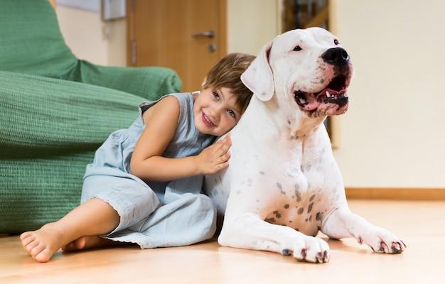 Niña bonita niño en el piso con perro