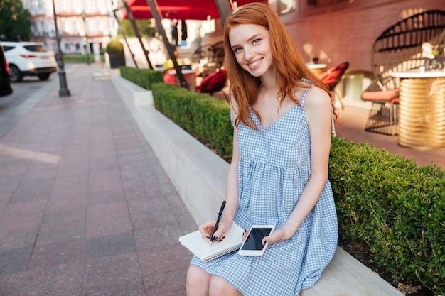 Niña bonita pelirroja sonriente sosteniendo teléfono móvil