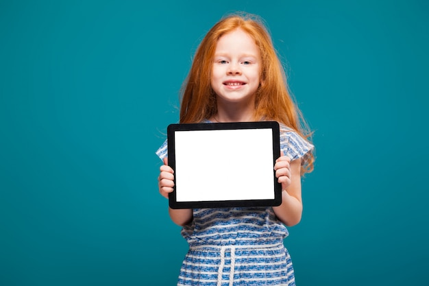 Niña bonita con el pelo rojo largo sostener pantalla en blanco ipad o tableta