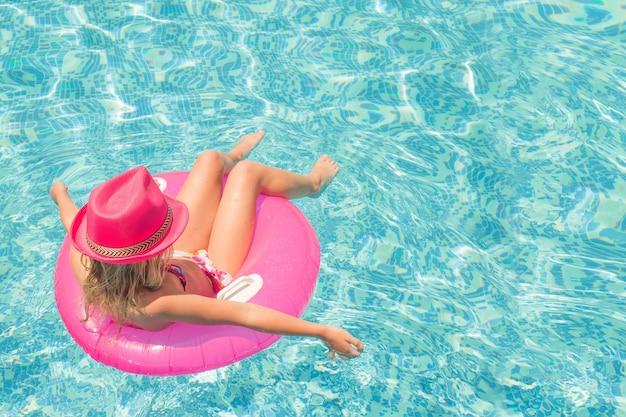 Niña bonita en piscina, vacaciones de verano.