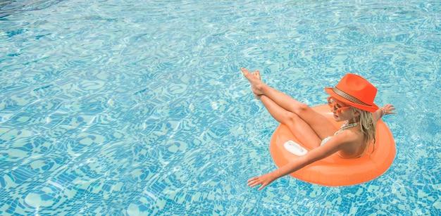Niña bonita en la piscina, vacaciones de verano.