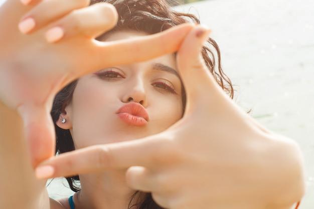 Niña bonita en la playa haciendo un selfie con sus manos en la cámara. hermosa chica en horario de verano