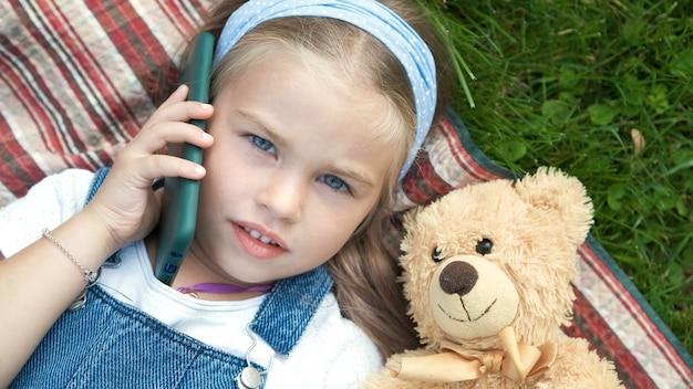 Niña bonita recostada sobre una manta sobre césped verde en verano con su osito de peluche hablando por teléfono móvil.