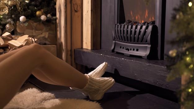 Niña bonita sentada junto a la chimenea con el telón de fondo del árbol de navidad