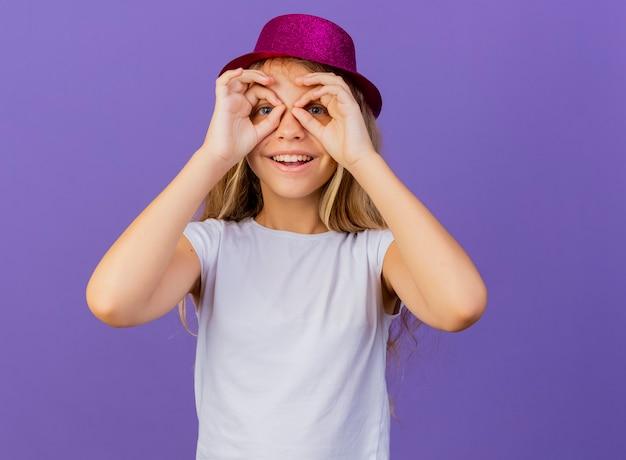 Niña bonita con sombrero de fiesta mirando a través de los dedos haciendo gesto binocular sonriendo, concepto de fiesta de cumpleaños de pie sobre fondo púrpura